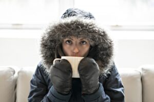 woman-wearing-parka-and-drinking-out-of-mug-inside-home