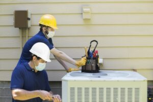 two-technicians-working-on-outside-air-conditioner
